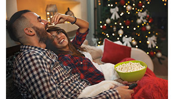 Young couple watching holiday TV specials while eating popcorn